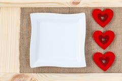 在用粗麻布报道的木头背景的心脏,白方块板材一张卡片为华伦泰` s天 免版税库存照片