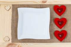 在用粗麻布报道的木头背景的心脏,白方块板材一张卡片为华伦泰` s天 库存照片