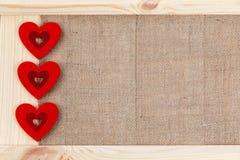 在用粗麻布报道的木背景,一张卡片的心脏为华伦泰` s天 免版税库存照片