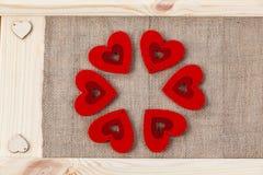 在用粗麻布报道的木背景,一张卡片的心脏为华伦泰` s天 库存照片