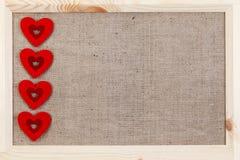在用粗麻布报道的木背景,一张卡片的心脏为华伦泰` s天 免版税图库摄影
