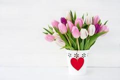 在用红色心脏装饰的白色花瓶的桃红色和白色郁金香花束 背景蓝色框概念概念性日礼品重点查出珠宝信函生活纤管红色仍然被塑造的华伦泰 库存照片