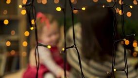 在用绿色云杉的分支装饰的屋子里弄脏愉快的母亲和可爱的婴孩画象在黄色诗歌选后 影视素材