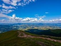 在用绿色密集的草盖的一座高山的土坎的土路上升到与云彩的蓝天 免版税库存图片