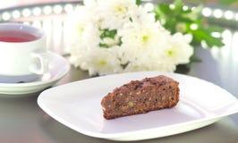 在用菊花装饰的一块白色板材的果仁巧克力蛋糕开花 库存照片
