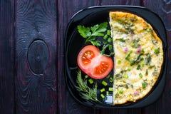 在用菜装饰的黑色的盘子的煎蛋卷 库存照片