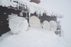 在用雪和冰盖的山的黑大厦,在寒冷期间在冬天 库存图片