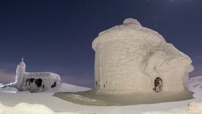 在用雪和冰盖的山的黑大厦,在寒冷期间在冬天 免版税库存图片