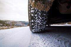 在用雪盖的冬天路的车胎 免版税库存图片
