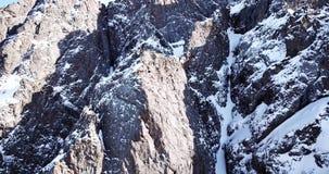 在用雪盖的寄生虫岩石的史诗飞行 在雪中的陡峭的岩石在山 影视素材