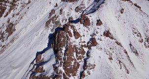 在用雪盖的寄生虫岩石的史诗飞行 在雪中的陡峭的岩石在山 股票视频