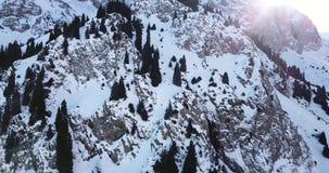 在用雪盖的寄生虫岩石的史诗飞行 在雪中的陡峭的岩石在山 股票录像
