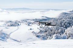 在用雪盖的山的寄生虫飞行 免版税图库摄影