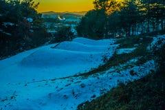 在用雪盖的山腰的三个埋葬土墩 免版税库存图片