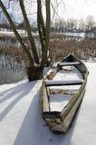 在用雪盖的湖海岸的老小船在冬天 免版税库存照片