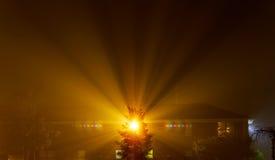 在用雾盖的夜街道上的公寓住宅块,城市的被弄脏的光通过朦胧的阴霾发光 图库摄影