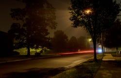 在用雾盖的空的夜城市街道上的公寓楼,被弄脏的城市光通过有薄雾的阴霾发光 图库摄影