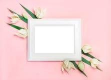 在用绿色叶子装饰的桃红色背景,文本的空白的白色木制框架 顶视图,平的位置 库存照片