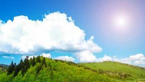 在用绿色木头盖的山的大白色云彩我 免版税库存图片