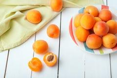 在用绿色餐巾装饰的一块美丽的板材的可口成熟有机橙色杏子放置在白色木桌 免版税库存图片