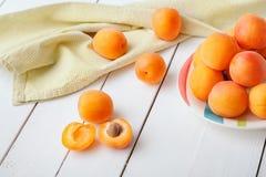 在用绿色餐巾装饰的板材的可口成熟有机橙色杏子放置在白色木桌 免版税库存照片