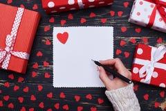 在用sm装饰的白色贺卡的女性手文字 库存照片