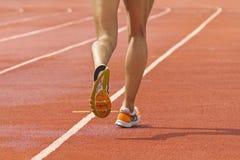 在田径运动体育场内跑的运动员 库存图片