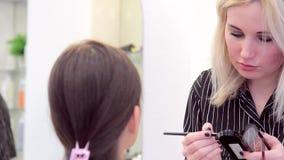在申请在模型的眼睛特写镜头的构成过程中面对化妆师 股票视频