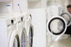 在电器商店和defocused买家的洗衣机 库存图片