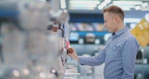 在电器商店,厨房技术员在他的手上选择搅拌器并且考虑设计和 影视素材