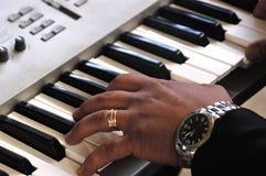 在电子口琴的手 免版税图库摄影