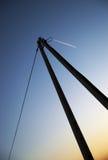 在电子杆上的飞行飞机在橙色蓝色天空 免版税库存照片