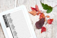在电子组织者的11月日历在木桌上 库存照片