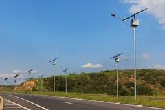 在电杆的太阳电池板在高速公路,对太阳能fo的用途 免版税库存图片