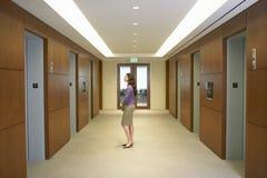 在电梯大厅的女性行政身分 免版税图库摄影