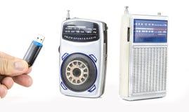 在电池的老和小晶体管收音机有USB钥匙的 免版税库存照片