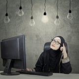 在电灯泡下的沉思女实业家 免版税库存图片
