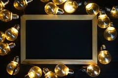 在电灯泡之间的黑板在黑木头 顶视图拷贝Spac 库存照片