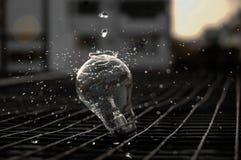 在电灯泡的倾吐的水 免版税图库摄影