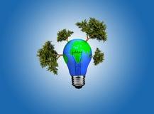 在电灯泡的地球在蓝色背景 免版税库存图片