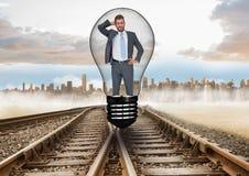 在电灯泡的迷茫的商人在轨道 免版税库存照片