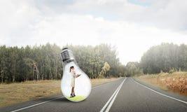 在电灯泡里面的女实业家 免版税图库摄影