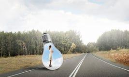 在电灯泡里面的女实业家 免版税库存照片