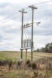 在电线杆的三台电业变压器 库存照片