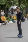 在电罗经skooter的可爱的女孩骑马在革命公园 库存图片