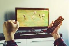 在电视上的人观看的足球比赛在家 免版税库存图片