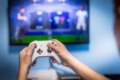 在电视乐趣游戏玩家使用和享用与被弄脏的屏幕的藏品比赛垫和控制器录影控制台的录影赌博和比赛戏剧 免版税库存照片