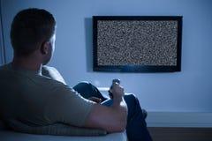 在电视前面的人没有信号 免版税库存图片