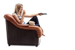 在电视和吃玉米花的妇女改变的渠道 免版税图库摄影