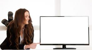 在电视屏幕显示附近的美丽的年轻女商人与另外的文本或图表的拷贝空间 免版税库存图片
